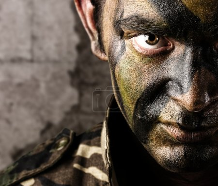 Photo for Young soldier face looking straight ahead againsta a grunge wall - Royalty Free Image