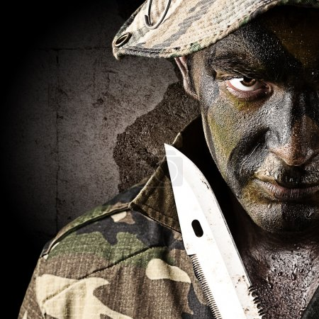 Photo for Portrait of young soldier threating to suicide against a grunge wall - Royalty Free Image