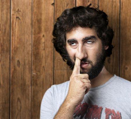 Photo pour Portrait de jeune homme avec le doigt dans le nez contre un mur de bois - image libre de droit
