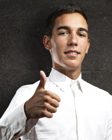 Photo for Young business man with thumbs up against a grunge wall - Royalty Free Image