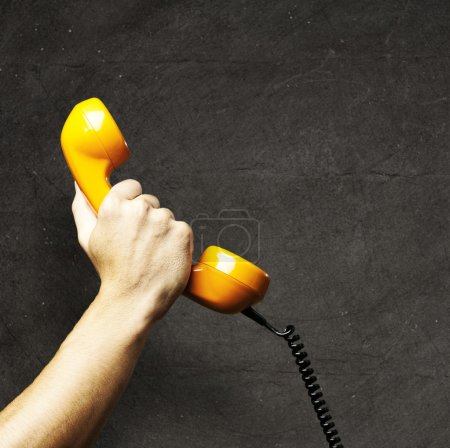 Photo for Hand holding a vintage telephone against a grunge background - Royalty Free Image