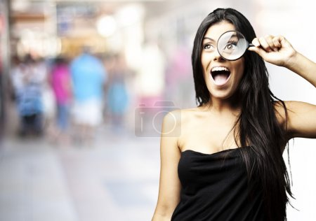 Photo for Portrait of young woman looking through a magnifying glass at a crowded place - Royalty Free Image