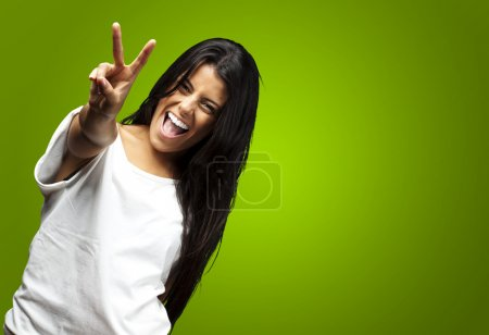 Photo for Portrait of young woman gesturing good against a green background - Royalty Free Image