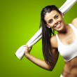 Portrait of a sporty young woman with towel agains...