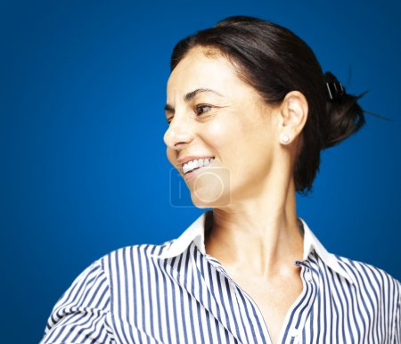Photo for Portrait of a middle aged woman smiling over blue background - Royalty Free Image