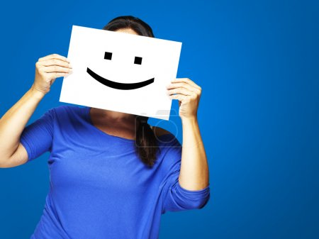 Photo for Woman showing a happy emoticon in front of face against a blue background - Royalty Free Image