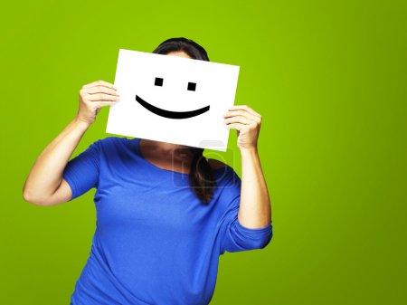 Photo pour Femme montrant un émoticône heureux devant le visage sur un fond vert - image libre de droit