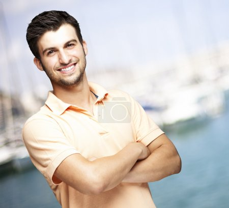 Photo for Portrait of a happy young man smiling against a harbor background - Royalty Free Image