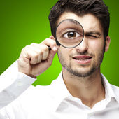 Portrait of young man looking through a magnifying glass