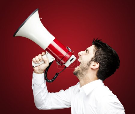 Photo for Portrait of young man screaming with megaphone - Royalty Free Image