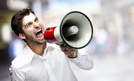 Photo for Portrait of a young man screaming with a megaphone - Royalty Free Image