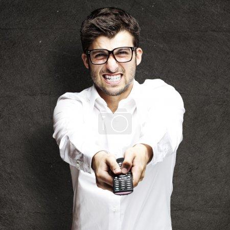 Photo pour Portrait de jeune homme en colère, à l'aide de la télécommande sur un fond grunge - image libre de droit