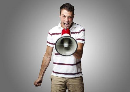 Photo pour Portrait de jeune homme criant avec mégaphone sur fond gris - image libre de droit