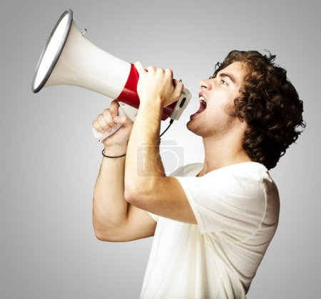 Photo for Portrait of a handsome young man shouting with megaphone against a grey background - Royalty Free Image