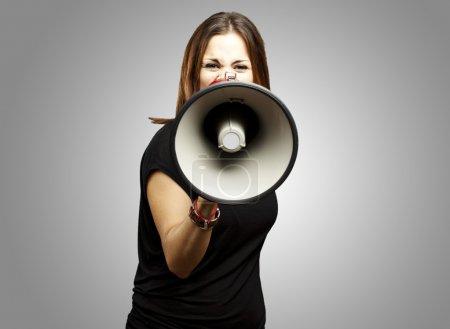 Photo pour Portrait de jeune femme criant avec mégaphone sur gris - image libre de droit