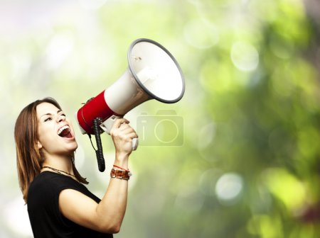 Photo for Portrait of middle aged woman shouting using megaphone against a nature background - Royalty Free Image