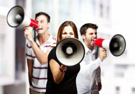 Foto de Retrato de un furioso grupo de empleados gritando utilizando megáfonos contra un fondo de ciudad - Imagen libre de derechos