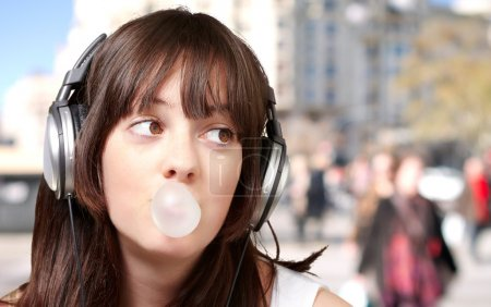 Portrait of young woman listening to music with bubble gum at cr