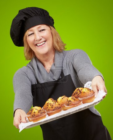 Portrait of cook woman showing a homemade muffins tray over gree