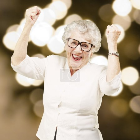 Portrait of a cheerful senior woman gesturing victory against a