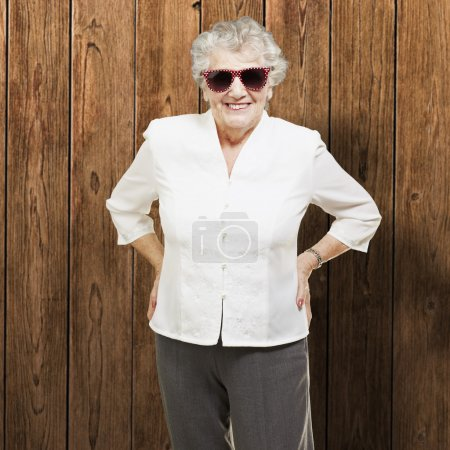 Portrait of senior woman standing wearing sunglasses against a w