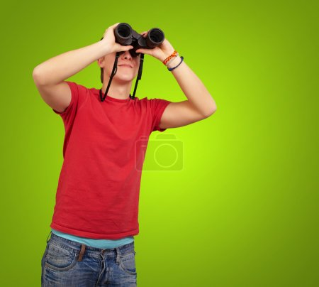 Portrait of young man with binoculars over green background