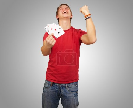 Photo for Portrait of young man doing a winner gesture playing poker over grey - Royalty Free Image