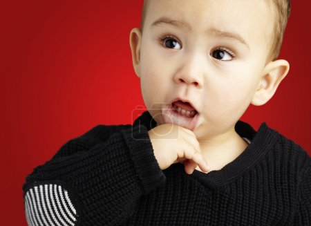 Portrait of a adorable thoughful kid against a red background