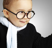 Portrait of adorable kid gesturing doubt against a grey backgrou