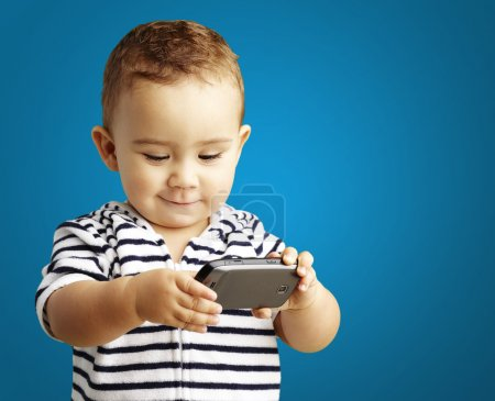 Photo for Portrait of a funny kid playing with a mobile - Royalty Free Image