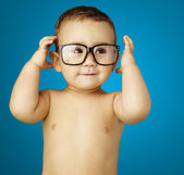 Portrait of funny kid shirtless wearing glasses over blue backgr