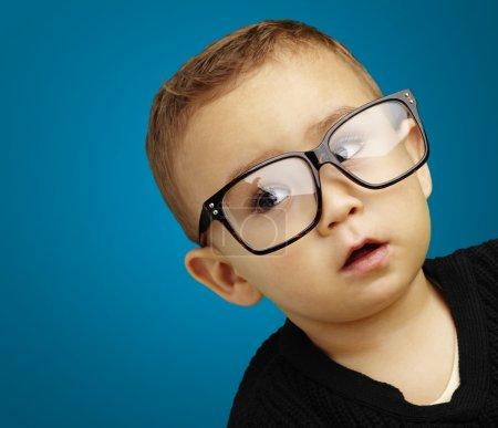 Portrait of kid wearing glasses over blue background