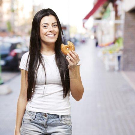 Foto de Mujer sosteniendo una rosquilla con una mordida contra un fondo calle - Imagen libre de derechos
