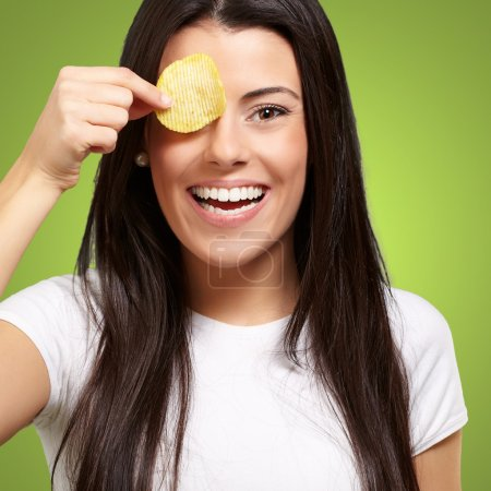 Portrait of young woman holding a potato chip in front of her ey