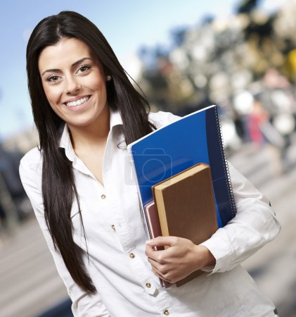 Pretty young woman smiling and holding notebooks against a stree