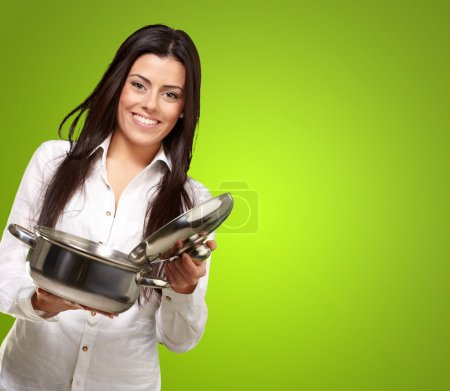Photo for Portrait of young girl opening sauce pan over green background - Royalty Free Image