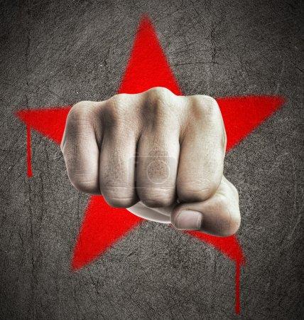 Photo pour Poing contre une étoile graffiti rouge sur un mur de béton, représentant la révolution et le communisme - image libre de droit
