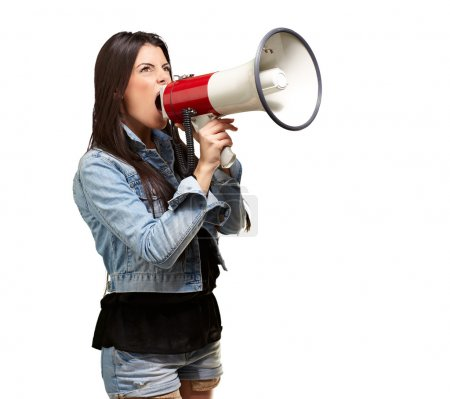 Portrait of young woman screaming with megaphone against a white