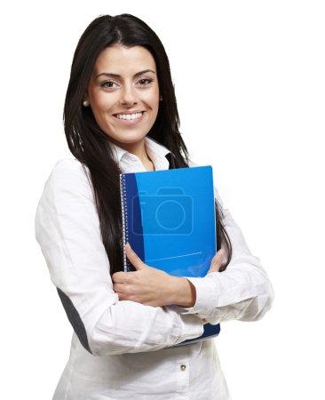 Photo pour Jeune femme souriante et tenant un carnet sur fond blanc - image libre de droit