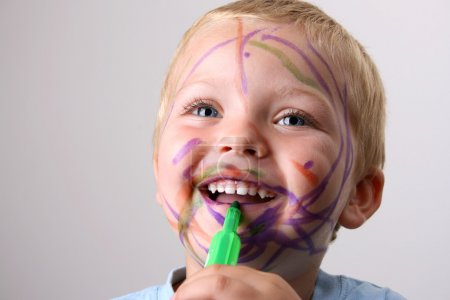 Photo for Laughing Toddler playing with colored pens making a mess - Royalty Free Image