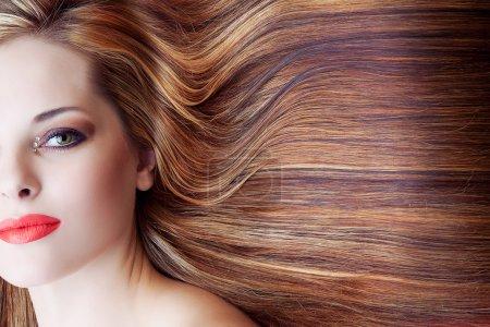 Photo pour Belle femme avec un maquillage artistique et un long fond de cheveux bruns brillants - image libre de droit