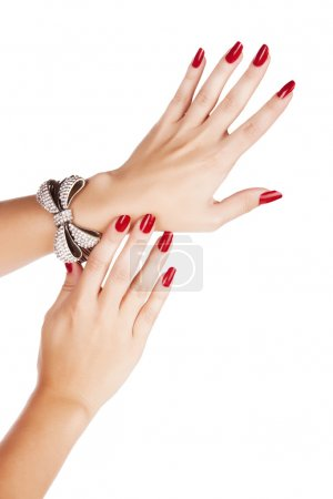 Photo for Closeup hands of young woman with red manicure polished nails wearing diamante bow bracelet - Royalty Free Image