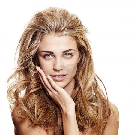 Photo pour Belle femme souriante aux longs cheveux bouclés blonds et au maquillage naturel sur fond blanc touchant son visage - image libre de droit