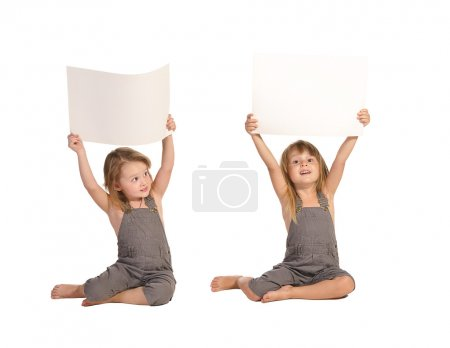 Twins sisters in rompers holding blank paper sheets isolated on