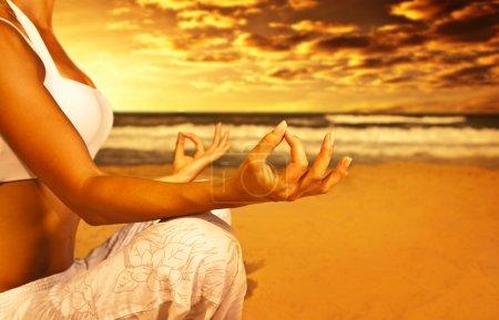 Photo pour Méditation d'yoga sur la plage, le corps en bonne santé de la femme en paix, femme assise détendue sur le sable au coucher de soleil magnifique sur la mer, fille calme et appréciant la nature, mode de vie de vacances actives, concept de bien-être, spa zen - image libre de droit