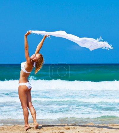 Photo pour Sautant et dansant fille heureuse sur la plage, fit sportif sain sexy en bikini, femme bénéficie de vent, vacances, liberté, plaisir de summertime concept - image libre de droit