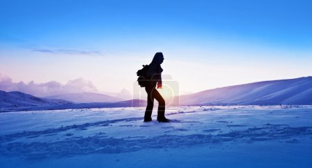 Photo for Woman traveler hiking in winter mountains, trekking in wintertime cold snowy weather, girl silhouette over natural blue sky with bright sunset and beautiful lan - Royalty Free Image