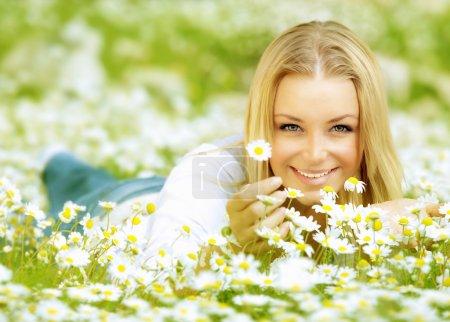 Beautiful girl enjoying daisy field