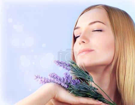 Photo pour Jeune femme appréciant le parfum de fleur de lavande, gros plan sur le visage féminin de peau propre, fille sensuelle à l'aromathérapie spa, traitement de la santé et de beauté, concept de bien-être - image libre de droit