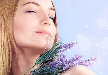 Photo pour Jeune femme appréciant le parfum de fleur de lavande, gros plan sur le visage féminin de peau propre, fille sensuelle à l'aromathérapie de spa, traitement de santé et de beauté, concept de bien-être - image libre de droit